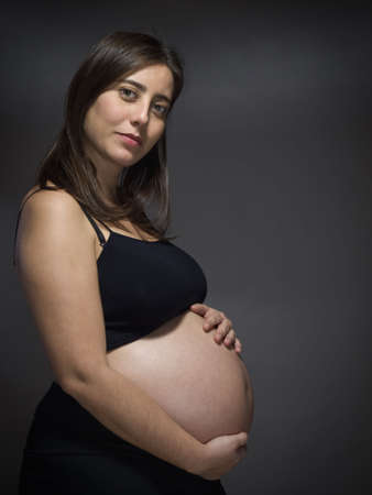 A pregnant woman holds her big belly over a gray background. Stock Photo - 6611359