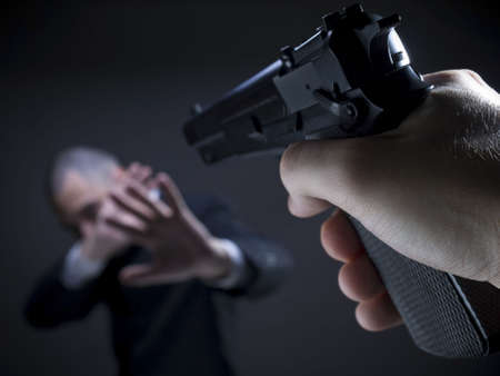 A threatening hand pointing a gun on an unarmed helpless businessman.
