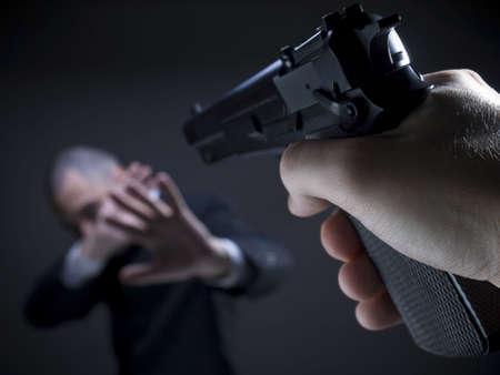 helpless: A threatening hand pointing a gun on an unarmed helpless businessman.