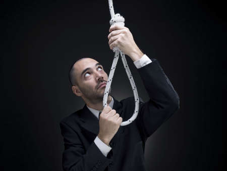 A businessman is setting up a noose.