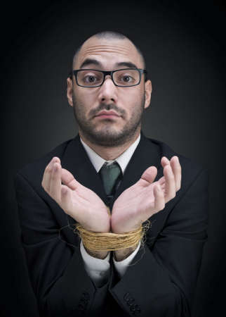 A man on a suit shows his tied hands with a puzzled expression.