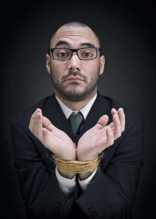 atados: Un hombre en un traje muestra sus manos atadas con una expresi�n perpleja.