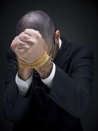 gefesselt: Ein Mann auf einer Farbe ist seine gebundene H�nde ausl�sen.