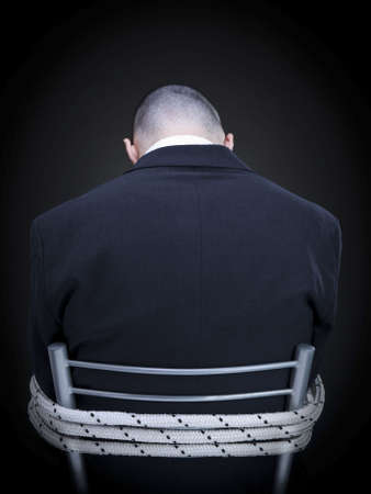 A businessman is tied up on a chair turning his back to the camera. photo