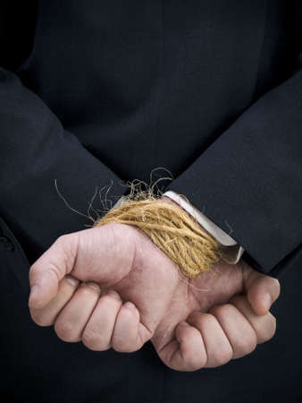 Closeup on a businessmans tied up hands.