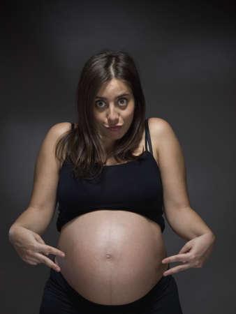 mother to be: Una madre per essere illustrato nello stomaco con due dita, come se lei era in attesa di due gemelli.