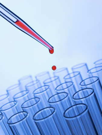 shallow: Close up of a pipette dropping a red sample into a test tube.
