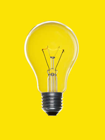 A light bulb over a yellow background. Tungsten glowing filament. photo