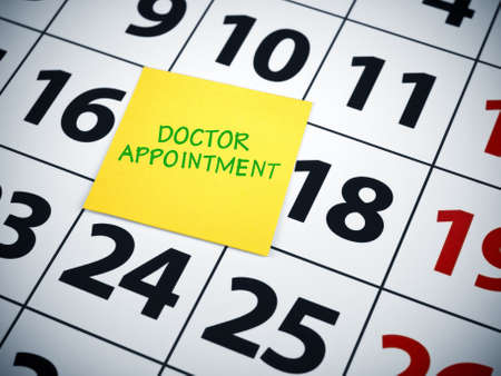 appointment: Doctor appoinment written on a sticky note on a calendar.