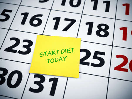 Start diet today written on a sticky note on a calendar. Stock Photo