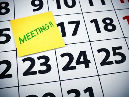 Meeting written on a sticky note on a calendar. photo