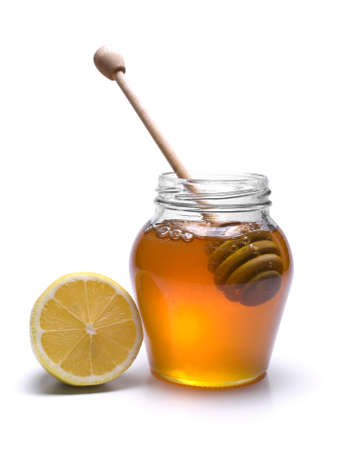 drizzler: Jar of honey with a wooden drizzler and a lemon. Isolated on white background.