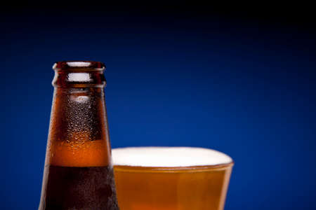 Close up on a bottle of beer and a full glass. Stock Photo - 22224444