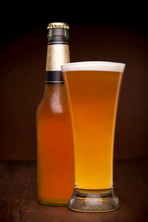 honey blonde: A glass and a bottle of beer on a wooden table.