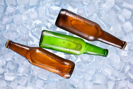 chilled: Three bottles of beer cooling on ice. Stock Photo