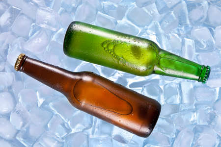 chilled: Two bottles of beer cooling on ice. Stock Photo