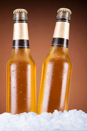 Two beer bottles sitting on ice over a brown background. photo