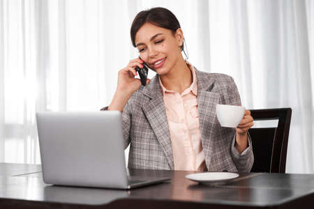 Businesswoman remote homework concept. Woman with a laptop. A young woman is talking on the phone and drinking coffee.