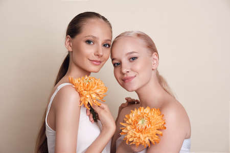 Women. Portrait of beauty and flowers. A group of models with flowers standing together. Girls with healthy, radiant and hydrated skin