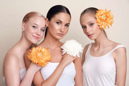 Women. Portrait of beauty and flowers. A group of models with flowers standing together looking at the camera on a beige background. Girls with healthy, radiant and hydrated skin