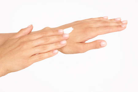 Female hands with cream. Close up of female hands applying cream on a white background Фото со стока
