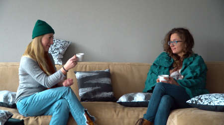 Two female friends chatting over coffee on sofa at home