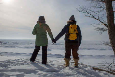 Two woman holding hands with backs turned on frozen lake shore Stock Photo