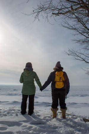Two woman holding hands with backs turned on frozen lake shore portrait Stock Photo