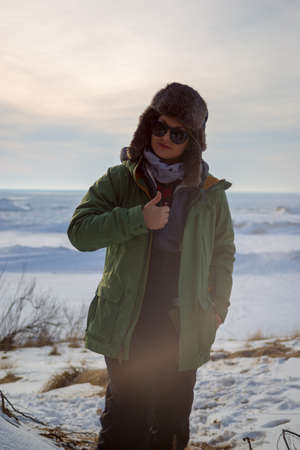 woman in sunglasses giving thumbs up at on frozen lake shore Stock Photo