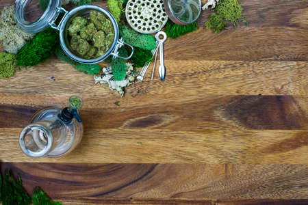 Marijuana in glass jar surrounded by moss, grinder, tool and bong with wooden background Stock Photo