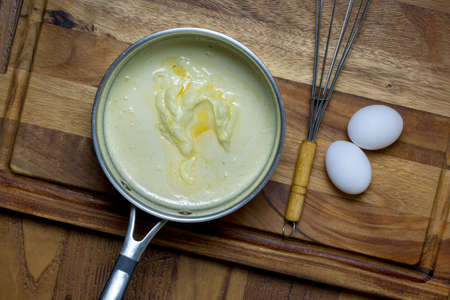 Cream in metal sauce pot with eggs and whisk with wooden cutting board