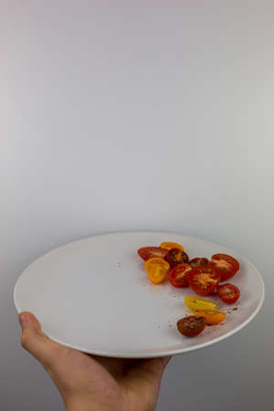 Isolated hand holding plate with sliced tomates with white background