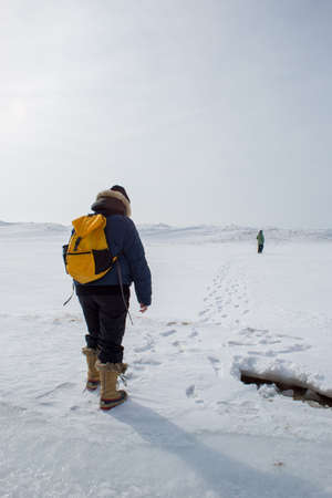 Woman wearing yellow backpack hiking in wintery landscape with woman in distance Stock Photo