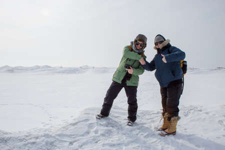 two women shaking hands surrounded by ice and snow