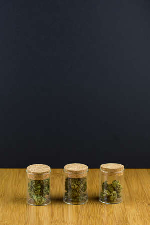 Glass jars filled with medical marijuana in a row on a bamboo table with black background in portrait Stock Photo