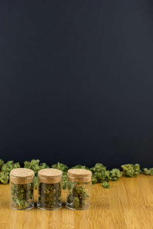 Glass jars filled with medical marijuana in a row with loose marijuana behind on a bamboo table against black background in portrait