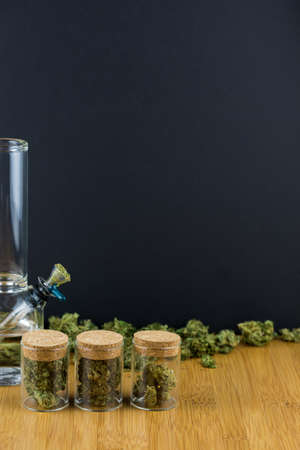 Glass jars filled with medical marijuana in a row with loose marijuana behind with glass bong on a bamboo table with black background in portrait Stock Photo