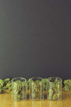Medical marijuana in glass jars with loose bud on bamboo table against a black background