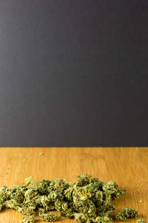 Medical marijuana scattered on a bamboo table against a black background in portrait