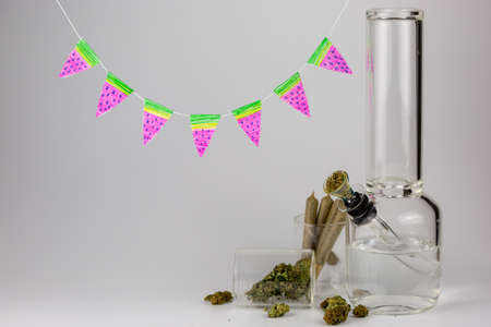 Bong with weed buds, joints and hand crafted watermelon pennants against white Stock Photo