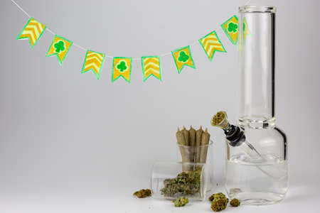 Weed buds in glass jar with cone joints, packed bong and hand crafted St. Patricks day pennants against a white backdrop Stock Photo