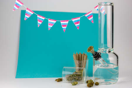 Glass bong with weed buds and cone joints in glass jars with festive red, white and blue pennants against blue and white backdrop
