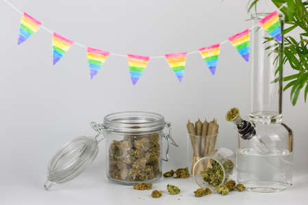 Assorted weed in glass jars with packed bong, tropical plant and hand crafted rainbow pennants