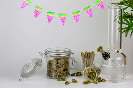 Assorted weed in glass jars with packed bong, cone joints, tropical plant and watermelon pennants