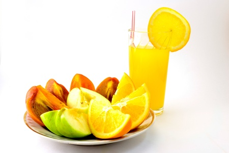 expanded: bright orange orange juice in faceted glass on a white background with light lying next to an orange