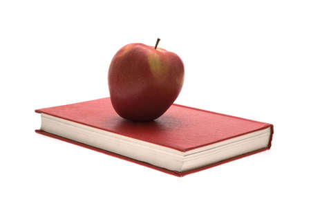 A red apple on an old red book.