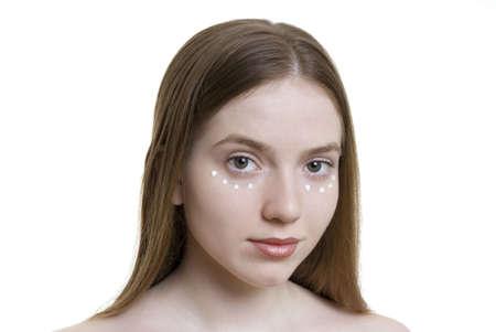 Eine junge sch�ne Frau mit Sahne f�r die Augenlider. Lizenzfreie Bilder