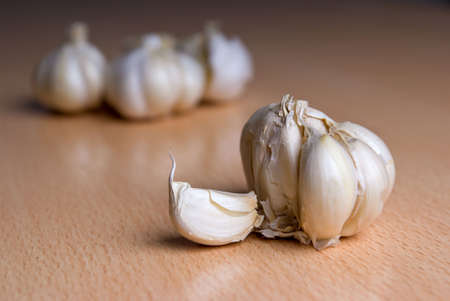 Garlic lying on a kitchen wooden table Stock Photo