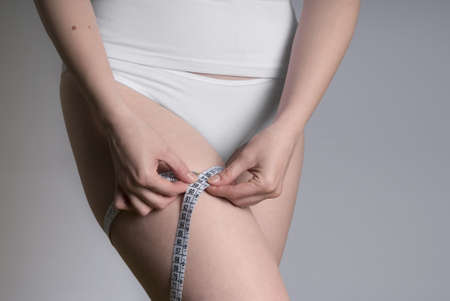 A girl measuring her haunch with a meauring tape