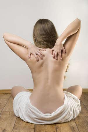 Slim donna seduta per terra toccando la schiena. Archivio Fotografico